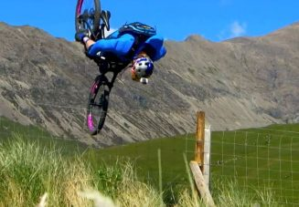 Danny MacAskill flipping over a fence.